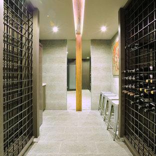 Réalisation d'une cave à vin design avec un sol en carrelage de porcelaine et des casiers.