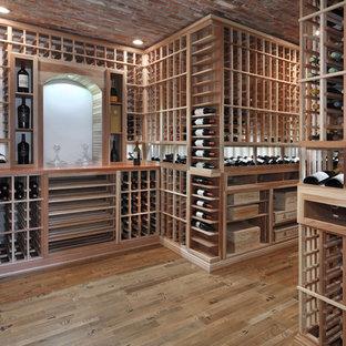 Wine cellar - transitional medium tone wood floor and brown floor wine cellar idea in Orange County with storage racks