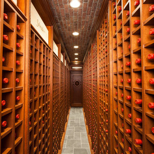 Expansive traditional wine cellar in New York with display racks and grey floors.