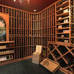 Klassisk inredning av en stor vinkällare, med skiffergolv, vinhyllor och svart golv