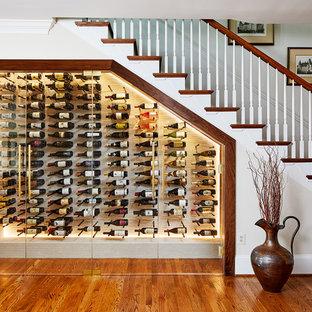 Klassisk inredning av en vinkällare, med mellanmörkt trägolv, vinhyllor och orange golv