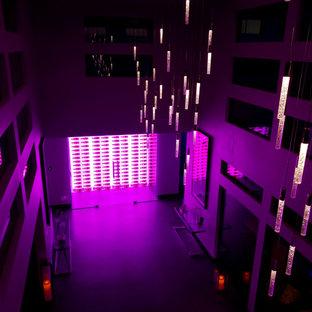Ispirazione per una cantina minimalista di medie dimensioni con pavimento in cemento, portabottiglie a vista e pavimento grigio