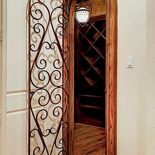 ヒューストンの大きい地中海スタイルのおしゃれなワインセラー (無垢フローリング、ワインラック、茶色い床) の写真