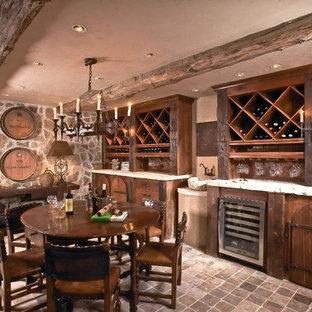Medelhavsstil inredning av en stor vinkällare, med tegelgolv, vinställ med diagonal vinförvaring och rött golv