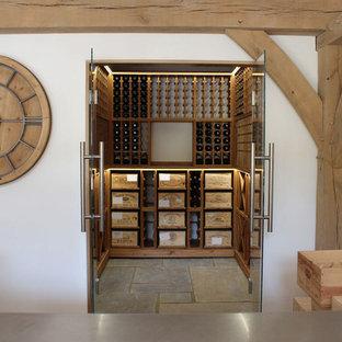 Diseño de bodega de estilo de casa de campo, de tamaño medio, con suelo de baldosas de cerámica, botelleros y suelo gris