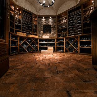 Foto de bodega clásica, grande, con suelo de ladrillo, botelleros y suelo naranja