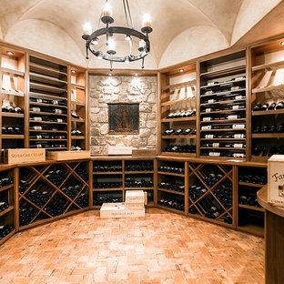 Large traditional wine cellar in New York with brick flooring, storage racks and orange floors.