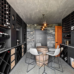 This is an example of a contemporary wine cellar in Sunshine Coast with concrete floors, storage racks and grey floor.