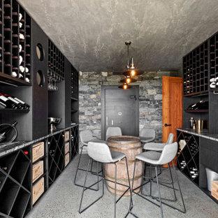 Bild på en funkis vinkällare, med betonggolv, vinhyllor och grått golv