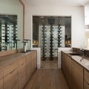 Cette image montre une grand cave à vin design avec un sol en bois brun, un présentoir et un sol beige.