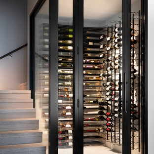 Wine cellar - mid-sized contemporary light wood floor and brown floor wine cellar idea in Miami with storage racks
