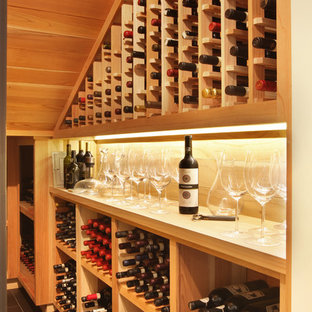 Design ideas for a small midcentury wine cellar in Orange County with porcelain flooring, storage racks and grey floors.