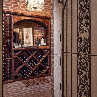 Foto på en stor vintage vinkällare, med tegelgolv, vinhyllor och rött golv