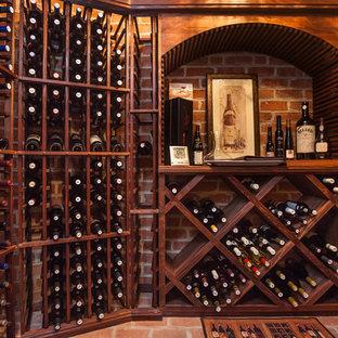 Diseño de bodega clásica, grande, con suelo de ladrillo, botelleros y suelo rojo