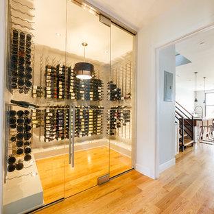 Réalisation d'une grand cave à vin design avec un sol en bois clair, un présentoir et un sol jaune.