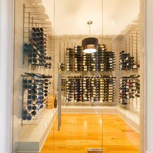 Réalisation d'une cave à vin design de taille moyenne avec un sol en bois clair, un présentoir et un sol jaune.
