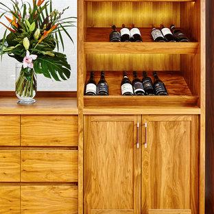 Imagen de bodega clásica renovada, pequeña, con suelo de madera en tonos medios y botelleros