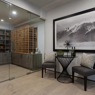 Ejemplo de bodega minimalista, de tamaño medio, con suelo de madera clara y vitrinas expositoras