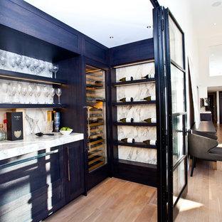 トロントの中くらいのトランジショナルスタイルのおしゃれなワインセラー (無垢フローリング、ディスプレイラック、ベージュの床) の写真