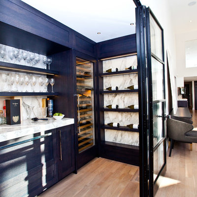 Example of a mid-sized transitional medium tone wood floor and beige floor wine cellar design in Toronto with display racks