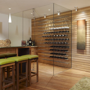 This is an example of a contemporary wine cellar in Other with orange floors.