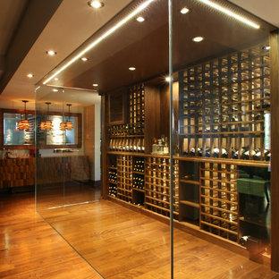 Minimalist medium tone wood floor and yellow floor wine cellar photo in Toronto with storage racks