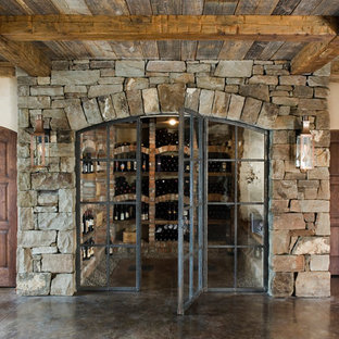 This is an example of a medium sized rustic wine cellar in Other with concrete flooring, display racks and brown floors.