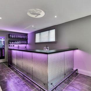 Immagine di una cantina minimalista di medie dimensioni con pavimento in gres porcellanato, portabottiglie a vista e pavimento nero
