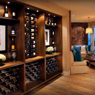 Cette photo montre une cave à vin tendance de taille moyenne avec un sol en bois brun, des casiers et un sol jaune.