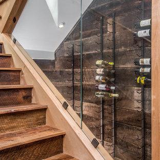 Idéer för att renovera en mellanstor rustik vinkällare, med mörkt trägolv, vinställ med diagonal vinförvaring och brunt golv