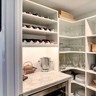 Imagen de bodega clásica, pequeña, con suelo de madera clara y botelleros