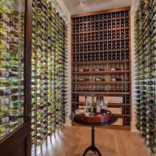 Imagen de bodega minimalista, grande, con suelo de madera en tonos medios y vitrinas expositoras
