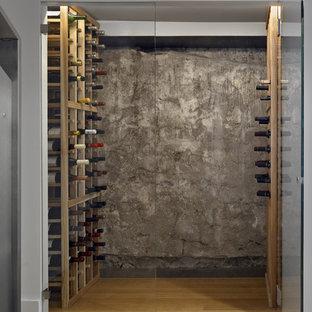 Modern inredning av en liten vinkällare, med mellanmörkt trägolv och vinhyllor