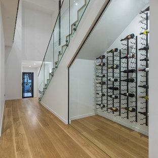 Idéer för att renovera en funkis vinkällare, med ljust trägolv, vinhyllor och gult golv