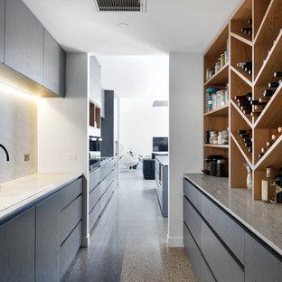 Ejemplo de bodega minimalista, de tamaño medio, con suelo de cemento, botelleros y suelo gris