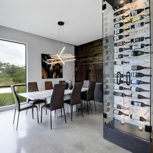 Esempio di una cantina contemporanea di medie dimensioni con pavimento in cemento, portabottiglie a vista e pavimento grigio