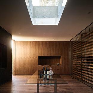 Minimalist medium tone wood floor and brown floor wine cellar photo in Los Angeles with storage racks