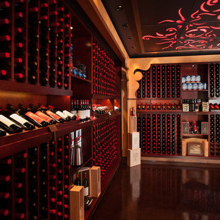 Foto på en stor orientalisk vinkällare, med betonggolv, vinhyllor och brunt golv