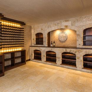 Foto de bodega mediterránea, extra grande, con suelo de piedra caliza, botelleros y suelo beige