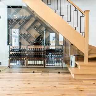 Inspiration för en mellanstor funkis vinkällare, med mellanmörkt trägolv, vinställ med diagonal vinförvaring och brunt golv