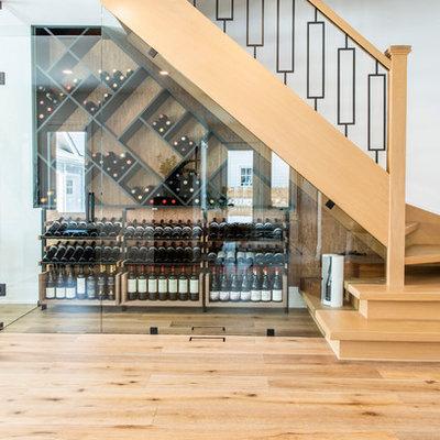 Mid-sized minimalist medium tone wood floor and brown floor wine cellar photo in Toronto with diamond bins