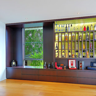 Idée de décoration pour une cave à vin design avec un sol en bois brun, un présentoir et un sol jaune.
