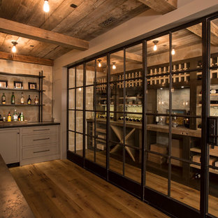 Wine cellar - large industrial medium tone wood floor wine cellar idea in Los Angeles with storage racks
