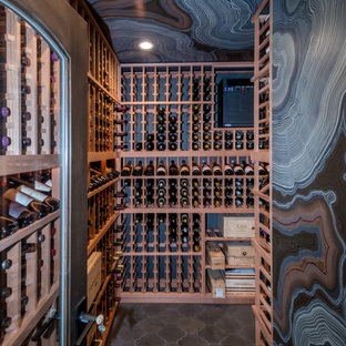 This is an example of a transitional wine cellar in San Francisco with storage racks and grey floor.