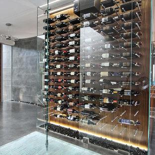 Bild på en mellanstor funkis vinkällare, med betonggolv, vindisplay och grått golv