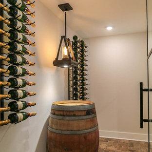 Imagen de bodega campestre, de tamaño medio, con suelo de ladrillo, botelleros y suelo beige