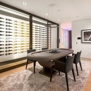 Immagine di una grande cantina moderna con parquet chiaro, portabottiglie a vista e pavimento beige