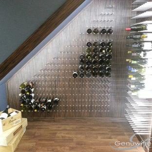 Imagen de bodega moderna, pequeña, con suelo de madera en tonos medios y botelleros