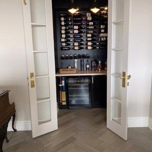 Diseño de bodega clásica renovada, pequeña, con suelo de madera clara, botelleros y suelo gris