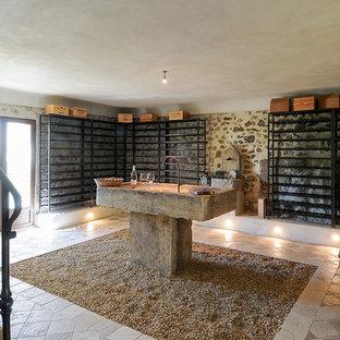 Imagen de bodega campestre, de tamaño medio, con suelo de piedra caliza, botelleros y suelo beige